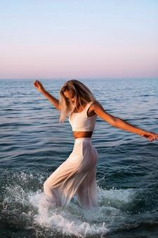 白いトップとズボンが濡れている日没の女性。ボヘミアンな衣装。