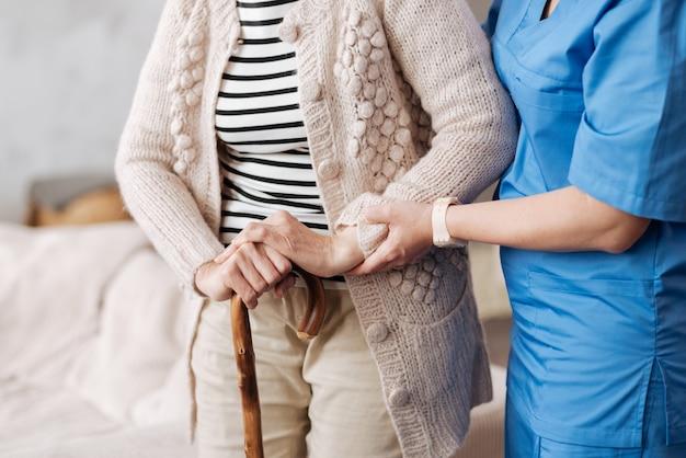 Закатные годы. замечательный аккуратный медицинский работник следит за тем, чтобы пожилая женщина стояла твердо, пока она пыталась прогуляться дома