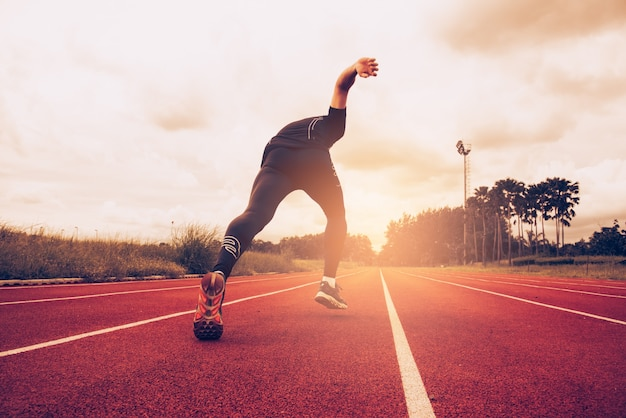 Sunset and young man running on lane. success and goal of business concept