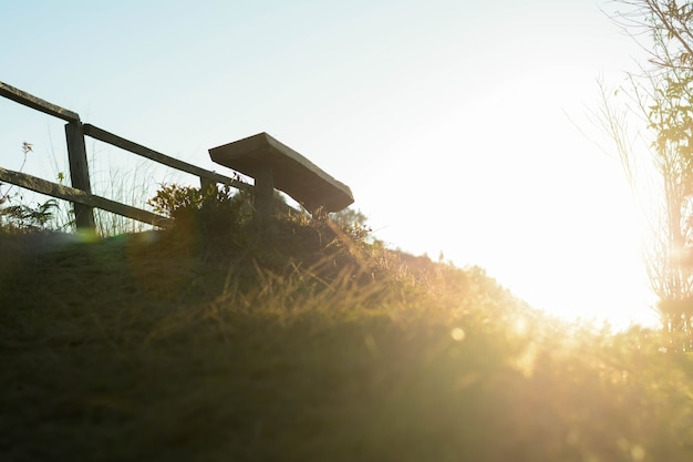The sunsets beautifully through the grass, fences, and chairs in the evening.