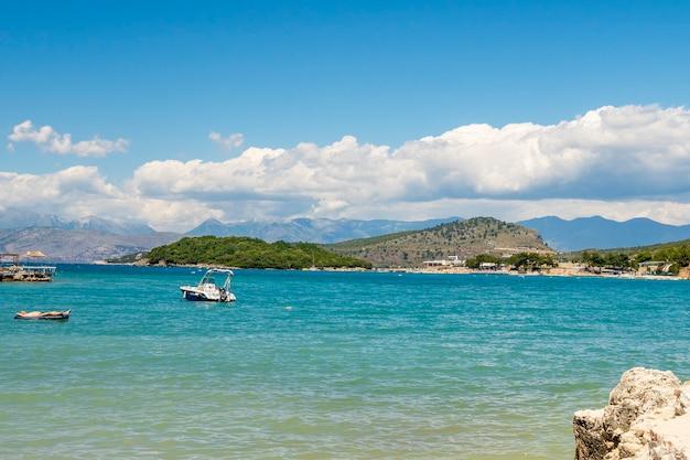 알바니아의 작고 아름다운 크사밀 해변에 있는 양산 파라솔과 야외용 데크의자. 프리미엄 사진