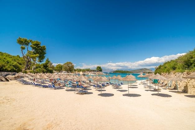알바니아의 작고 아름다운 크사밀 해변에 있는 양산 파라솔과 야외용 데크의자.