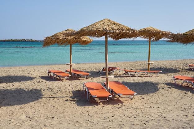 Зонтики на тропическом песчаном пляже на фоне бирюзовой морской воды.