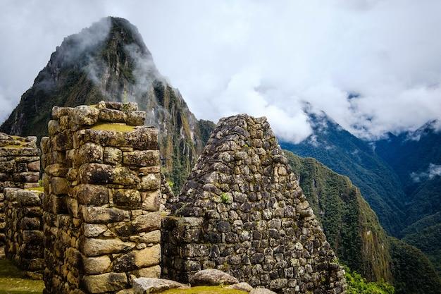 햇살이 가득한 산들 사이의 마추픽추 석조 벽과 사원의 숨막히는 전경...