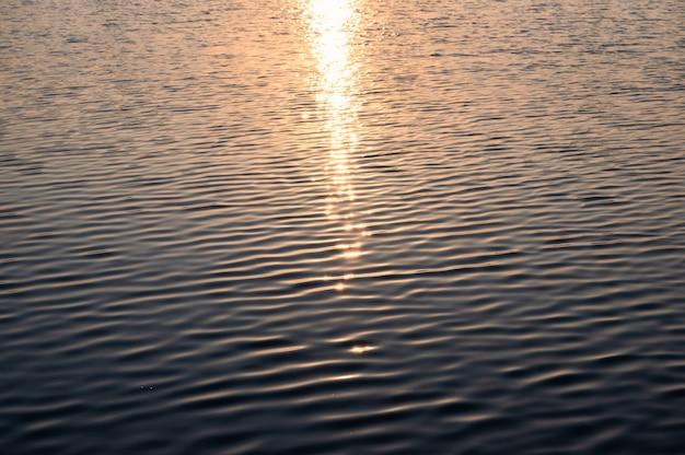朝、湖の波状の水に輝く太陽の光