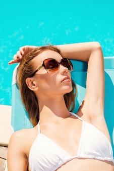 サンシャインは最高の薬です。プールの近くのデッキチェアでリラックスした白いビキニの美しい若い女性の上面図
