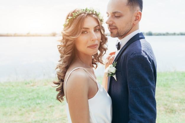 Sunshine portrait of happy bride and groom outdoor in nature