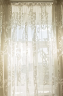 窓のある部屋の透明なチュールカーテンからの日差し