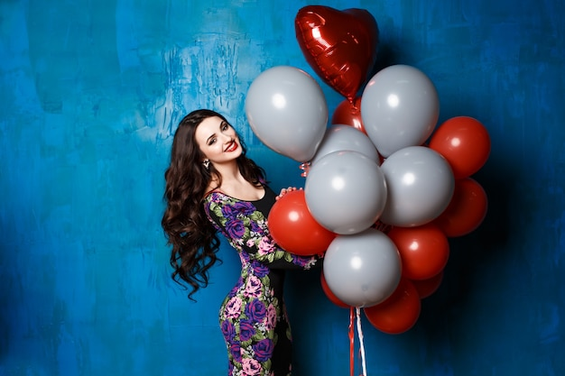 サンシャイン女性の肖像画、明るい色、面白い弓の髪型、赤い爪、赤い唇とファッションメイクの美容ファッション幸せな女の子。長く明るい花のドレスで明るい色の風船とブルネット