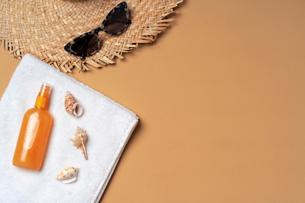 Suntan cosmetic product with towel, hat and sunglasses on beige background