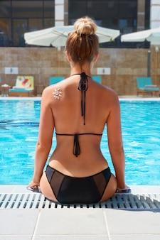 선탠 로션. 태양의 형태로 썬 스크린 태양 크림을 적용하는 아름 다운 여자. 태양 보호. 선크림. 피부 및 바디 케어.