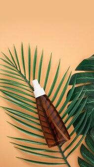 熱帯の葉と柔らかいオレンジ色の背景に日焼け止めローションボトル。上面図、コピースペース。日焼け止め化粧品、夏のスキンケアコンセプト