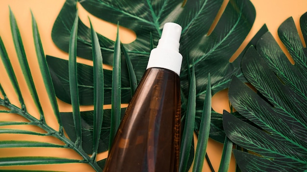 Suntan lotion bottle on soft orange background with tropical leaf. top view, copy space. sun protection cosmetic products, summer skin care concept