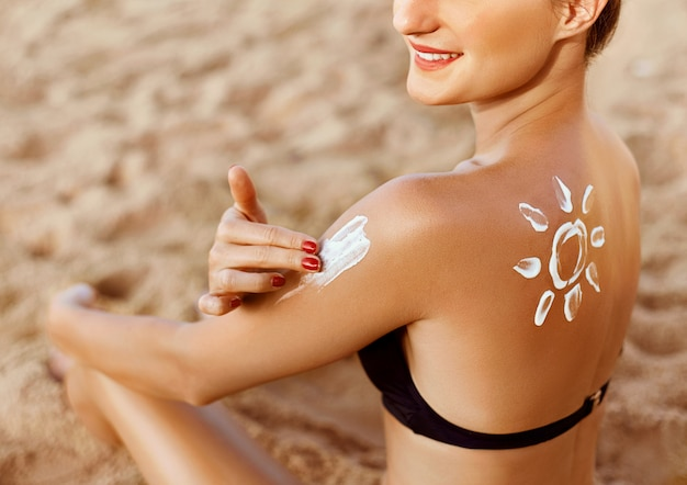 Suntan lotion. young woman applying sunscreen solar cream on the beach. sun shape on the shoulder.