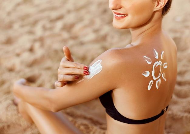 Лосьон для загара. молодая женщина, применяя солнцезащитный крем на пляже. форма солнца на плече.