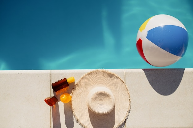 Suntan oil, hat and ball at the edge of the pool