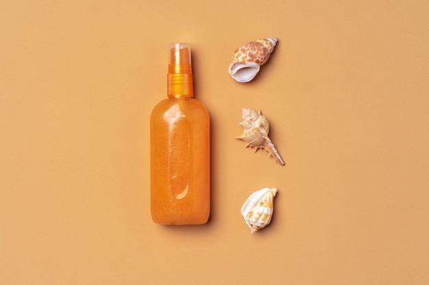 Suntan oil spray with seashells on beige, flat lay