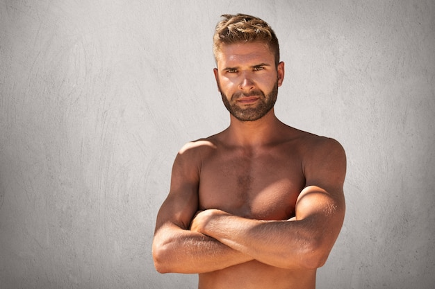 Suntanned confident man with stylish hairdo, bristle and appealing eyes, standing topless keeping hands crossed