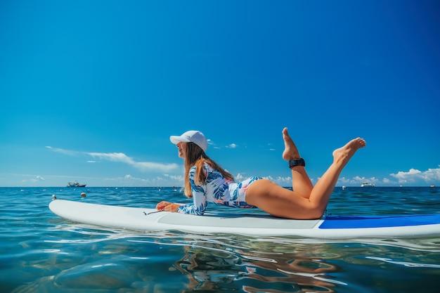 Sup встать доска весла молодая женщина, плывущая по красивому спокойному морю с кристально чистой водой