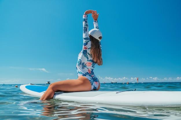 Sup встать доска весла молодая женщина плывет по красивому спокойному морю с кристально чистой водой