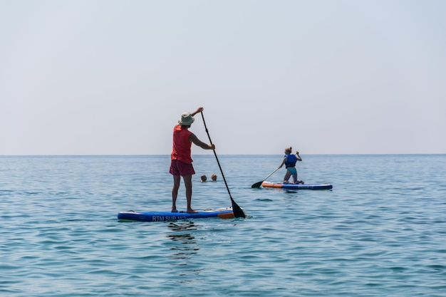 Туристы занимаются греблей на доске (sup) на поверхности спокойного моря.