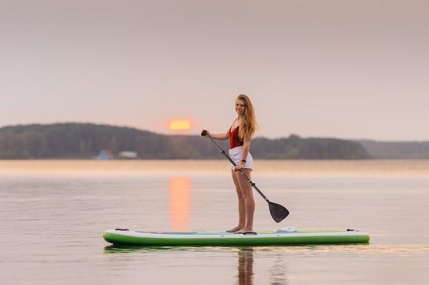 海の少女は、美しい夕日や日の出の水の色でパドルsupボードの上に立ちます。