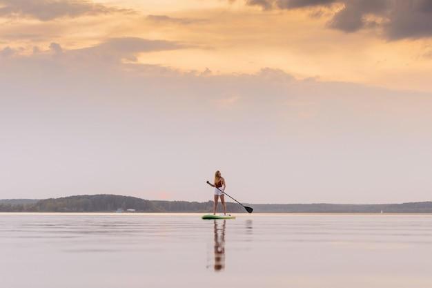 海の若い女性は美しい夕日や日の出の色でパドルsupボードに立ち上がる