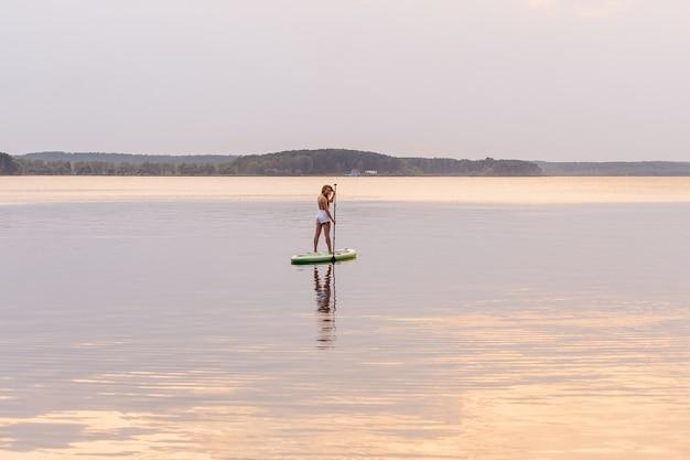 美しい夕日や日の出の色でパドルsupボードに立ち上がるの若い女性