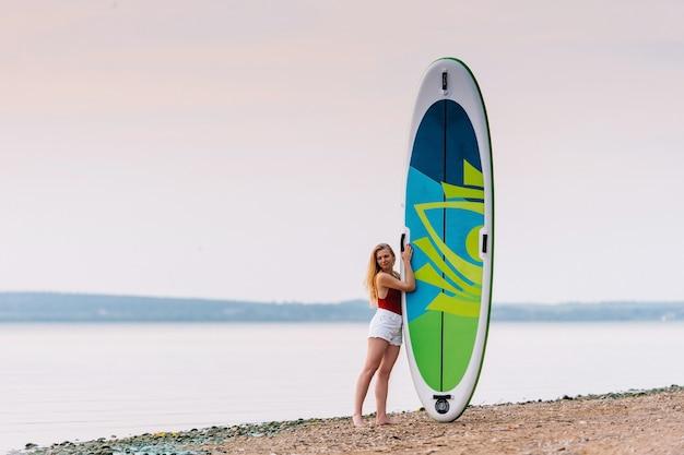 美しい夕日や日の出の色でパドルsupボードでビーチを立ち上がるのスリムな女性