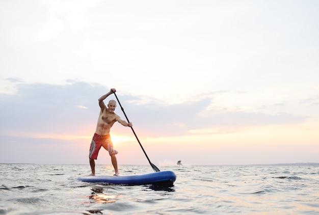 男は海の背景にsupボードの上に立つ