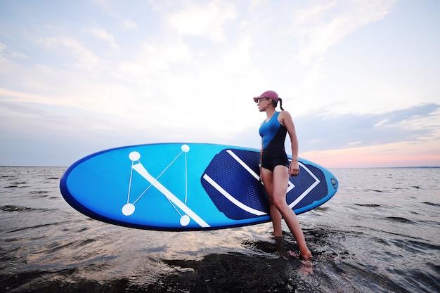 海と夕日の背景にsupボードを持つ若い女の子