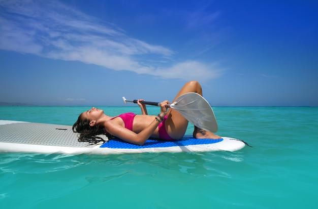 リラックスしたパドルサーフボードsupの上に横たわる少女
