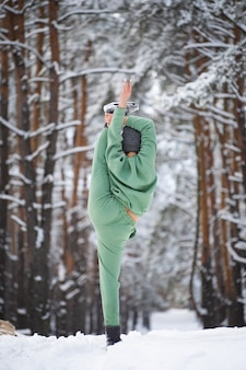 Super flexible woman doing split in the snowy park