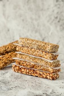Батончики мюсли для завтрака высшего качества с овсом, миндалем, тыквенными семечками, семенами льна, медом и финиками. плоская кладка с ингредиентами. с копией пространства.