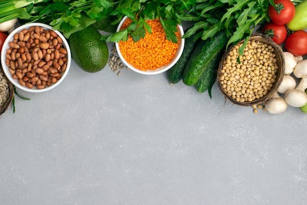 슈퍼 푸드 또는 채식 음식. 콘크리트 회색 배경에 건강 식품을 준비하기위한 땅콩, 렌즈 콩, 야채, 콩, 야채 채소
