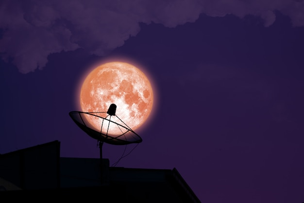 Super full harvest blood moon on night sky back satellite dish on the roof
