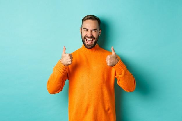 Очень хорошо. довольный счастливый человек показывает палец вверх, согласен с вами, хвалят отличную работу, смотрит