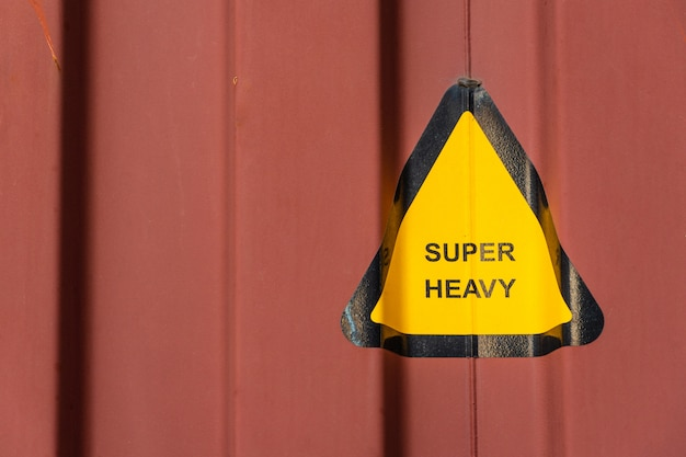 Super heavy warning sign of transport loading at construction site or factory warehouse