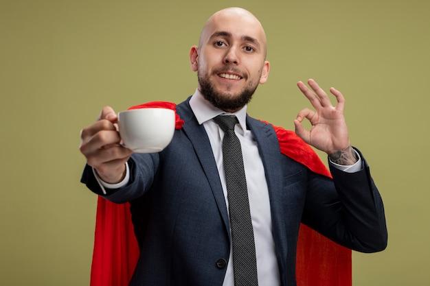슈퍼 영웅 수염이 밝은 녹색 벽 위에 서있는 확인 서명을 보여주는 커피 한잔 들고 빨간 케이프에서 비즈니스 남자