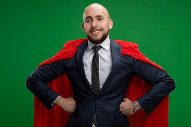 緑の壁の上に立っているヒップで腕に自信を持って笑って赤いマントのスーパーヒーローひげを生やしたビジネスマン