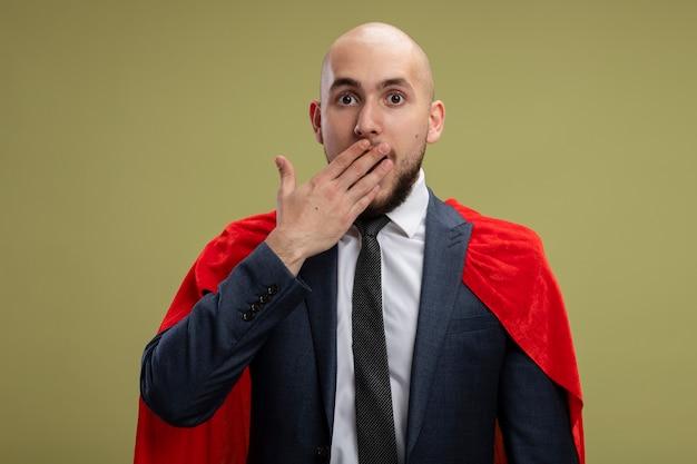 Uomo d'affari barbuto super eroe in mantello rosso che copre la bocca con la mano scioccata in piedi sopra la parete verde chiaro