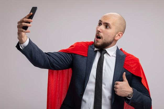 Uomo d'affari barbuto super eroe in mantello rosso facendo selfie utilizzando lo smartphone che mostra i pollici in su in piedi sopra il muro bianco