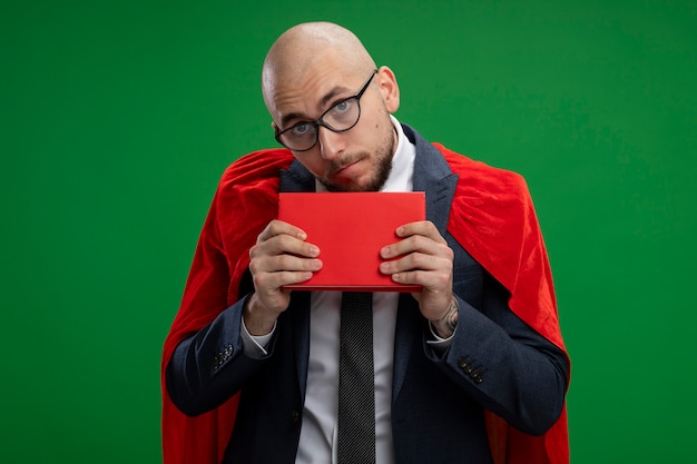 Super hero bearded business man in red cape holding book  confused and very anxious standing over green wall