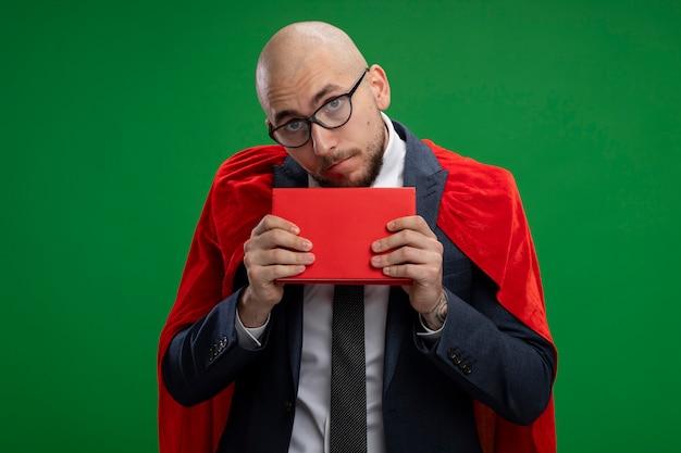 Uomo d'affari barbuto super eroe in mantello rosso che tiene libro confuso e molto ansioso in piedi sopra la parete verde