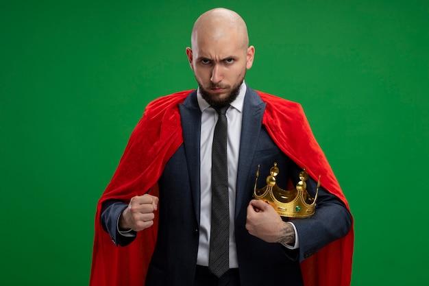 Uomo d'affari barbuto super eroe in mantello rosso che tiene corona lokign con il pugno chiuso arrabbiato in piedi sopra la parete verde