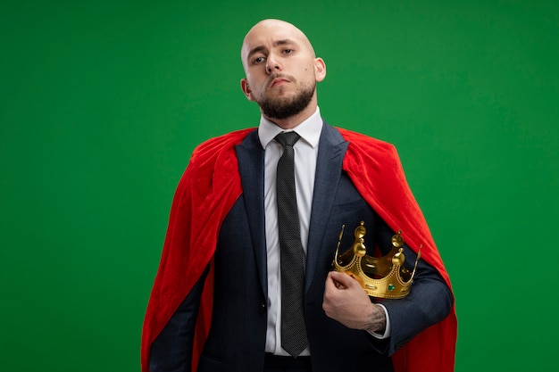 Uomo d'affari barbuto super eroe in mantello rosso che tiene corona guardando fiducioso in piedi sopra la parete verde