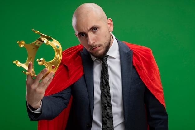 Uomo d'affari barbuto super eroe in mantello rosso che tiene la corona con la faccia seria in piedi sopra la parete verde