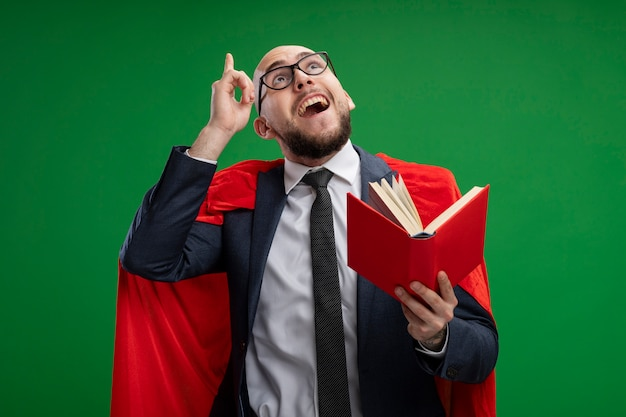 Super hero bearded business man in red cape holding open book looking up showing index finger having idea smiling standing over green wall