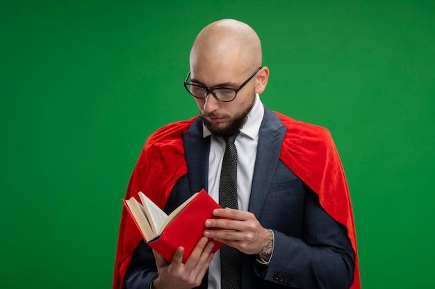 Uomo d'affari barbuto super eroe in mantello rosso che tiene la lettura del libro aperto in piedi sopra la parete verde