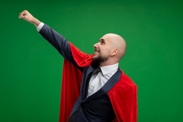Uomo d'affari barbuto super eroe in mantello rosso che fa il gesto vincente con la mano sorridente fiducioso pronto ad aiutare in piedi sopra la parete verde